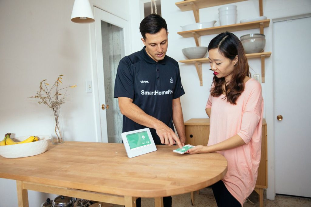 Vivint professional installer with home owner - giving home security instructions